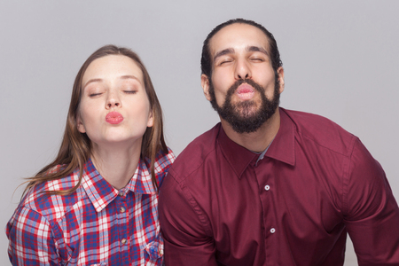 Portrait of funny bearded man with black collected hair and woman in casual style standing with closed eyes and kissing to camera. indoor studio shot, isolated on gray background. Archivio Fotografico