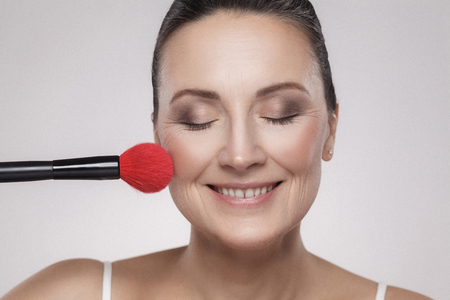 Closeup portrait of a attractive middle aged woman with perfect skin applying makeup with a red brush and toothy smile against a gray background. Indoor, studio shot, copy space, looking at camera