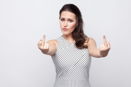 Portrait of angry young brunette woman with makeup and striped dress standing serious face and looking at camera and showing middle finger fuck sign. indoor studio shot, isolated on grey background. 스톡 콘텐츠