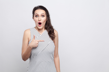 Portrait of beautiful amazed young brunette woman in striped dress standing and looking at camera with surprised face and pointing at copyspace. indoor studio shot, isolated on grey background