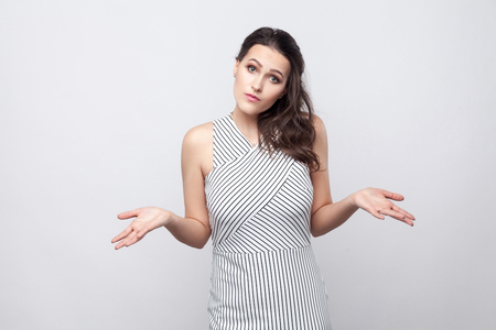 I dont know. Confused young brunette woman with makeup and striped dress standing and looking at camera with crossed hands and thinking what to do. indoor studio shot, isolated on grey background.