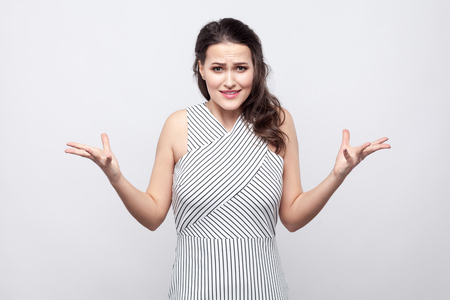 Portrait of confused beautiful young brunette woman with makeup and striped dress standing and looking at camera with angry face. indoor studio shot, isolated on grey background. Stock Photo