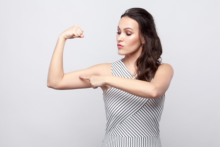 I am strong. Portrait of proud beautiful young brunette woman with makeup and striped dress standing and pointing at her biceps. indoor studio shot, isolated on grey background. 写真素材