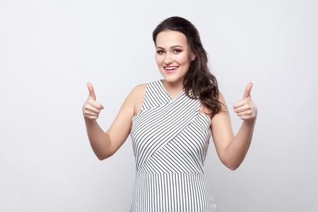 Portrait of happy satisfied beautiful young brunette woman with makeup and striped dress standing, toothy smiling and looking at camera with thumbs up. indoor studio shot, isolated on grey background.
