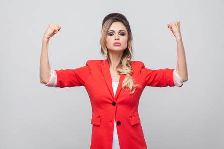 I am strong. Portrait of proud beautiful business lady with hairstyle and makeup in red fancy blazer, standing with raised arms and looking at camera. indoor studio shot, isolated on grey background.