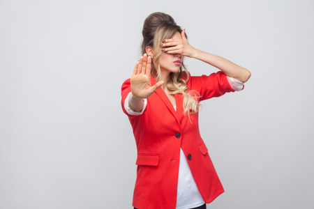 Stop, i dont want to see this. Portrait of beautiful business lady with hairstyle and makeup in red fancy blazer, standing covering her eyes with stop hands. studio shot, isolated on grey background. Banco de Imagens