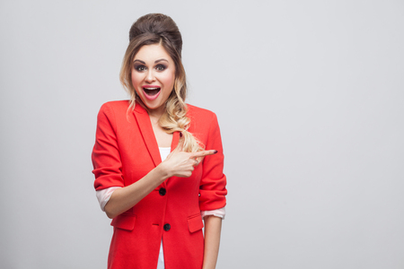 Portrait of excited beautiful business lady with hairstyle, makeup in red fancy blazer standing, looking at camera and pointing at copyspace and surprised. studio shot, isolated on grey background.