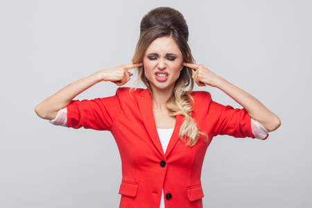 I don't want to hear. Nervous business lady with hairstyle and makeup in red fancy blazer, standing clenching teeth and puting finger in ears. indoor studio shot, isolated on grey background.