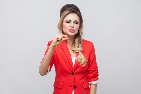 Give me a little bit more please. Beautiful business lady with hairstyle and makeup in red fancy blazer, standing and asking for a small thing more. indoor studio shot, isolated on grey background. Banco de Imagens