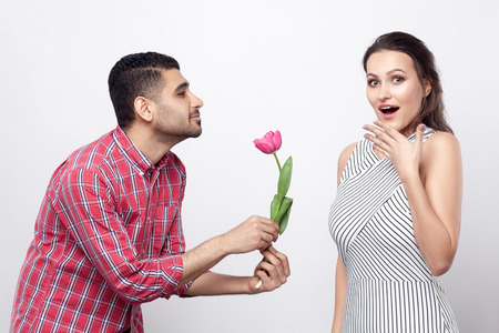 Side view man giving tulip to excited woman. Portrait of handsome man in red checkered shirt and beautiful woman in white striped dress standing. indoor studio shot, isolated on grey background.