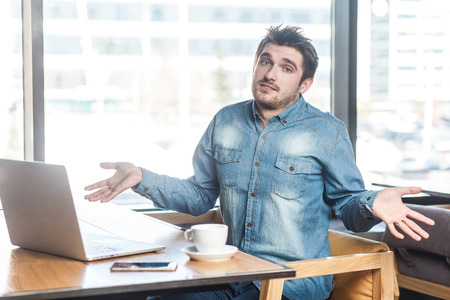 Not sure! Portrait of confused handsome bearded young freelancer in blue jeans shirt are sitting in cafe and working on laptop with raised arms and puzzled face, looking at camera. indoor Stock Photo