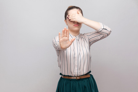 Stop, I don't want to see it. Portrait of beautiful young woman in striped shirt and green skirt standing, with stop gesture and covered her eyes. indoor studio shot, isolated on grey background.