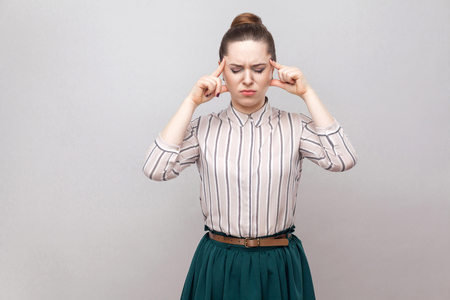 Headache. Portrait of unhappy beautiful young woman in striped shirt and green skirt and collected ban hairstyle, standing and holding her painful head. indoor studio shot, isolated on grey background