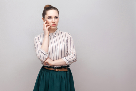 Confused beautiful young woman in striped shirt and green skirt with makeup and collected ban hairstyle, standing thoughtful and looking away. indoor studio shot, isolated on grey background.