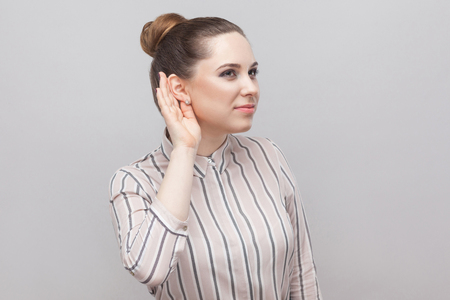 Closeup portrait of funny beautiful young woman in striped shirt and brown collected ban hairstyle, standing with hand near ear and trying to listen. indoor studio shot, isolated on grey background.