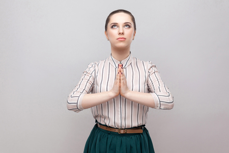 Portrait of hopeful beautiful young woman in striped shirt and green skirt with makeup and collected ban hairstyle, standing, looking uo and praying. indoor studio shot, isolated on grey background. Stock fotó