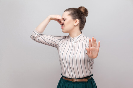 Portrait of ignoring beautiful young woman in striped shirt with makeup and collected ban hairstyle, standing with stop gesture and holding her nose. indoor studio shot, isolated on grey background.