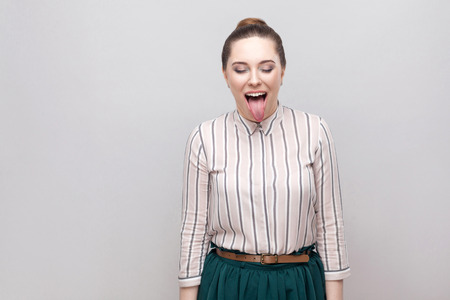 portrait of funny crazy beautiful young woman in striped shirt with makeup and collected ban hairstyle, standing with closed eyes and tongue out. indoor studio shot, isolated on grey background.