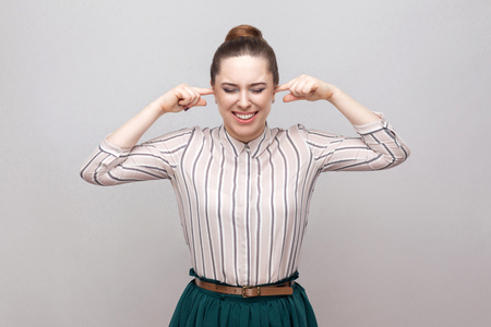 Portrait of unhappy beautiful young woman in striped shirt and green skirt with collected ban hairstyle, standing and putting her finger in ears. indoor studio shot, isolated on grey background.
