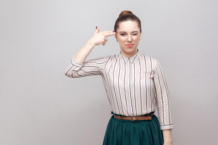 Portrait of crazy beautiful young woman in striped shirt and green skirt with makeup and collected ban hairstyle, standing with pistol gesture. indoor studio shot, isolated on grey background.