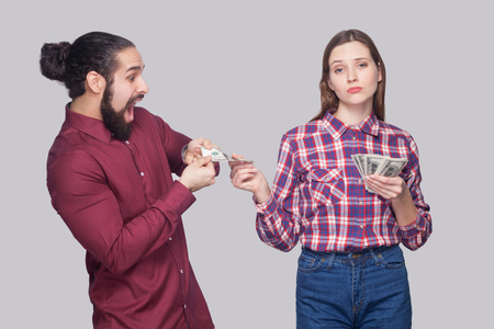 Portrait of rich serious woman with fan of money, sharing with amazed or surprised hungry man. standing and looking at camera like a boss. indoor studio shot, isolated on grey background.