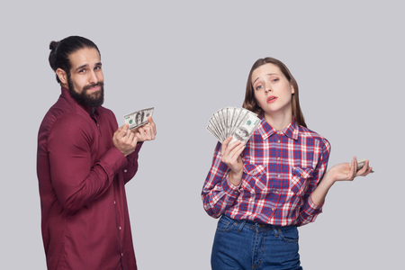 Portrait of rich serious woman with fan of money and near sad poor man, standing and looking at camera. indoor studio shot, isolated on grey background. Imagens