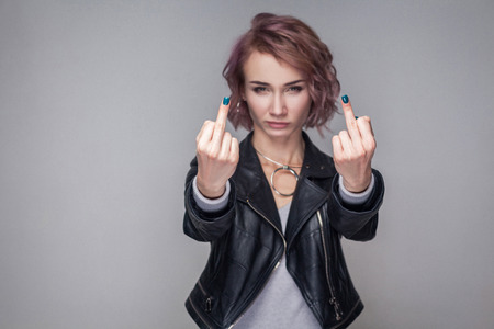 Portrait of aggressive girl with short hairstyle and makeup in casual style black leather jacket standing and looking at camera with middle finger. indoor studio shot, isolated on grey background.