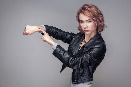 Portrait of serious beautiful girl with short hair and makeup in casual style black leather jacket standing, looking at camera and showing time gesture. indoor studio shot, isolated on grey background