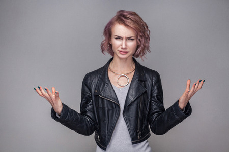 Portrait of confused beautiful girl with short hairstyle and makeup in casual black leather jacket standing with raised arms and looking at camera. indoor studio shot, isolated on grey background.
