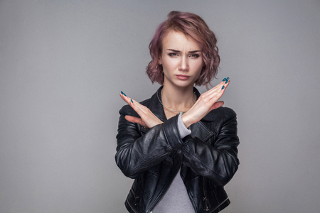 Portrait of serious woman with short hairs and makeup in casual style black leather jacket standing making X sign with her arms to stop doing something. indoor studio shot, isolated on grey background