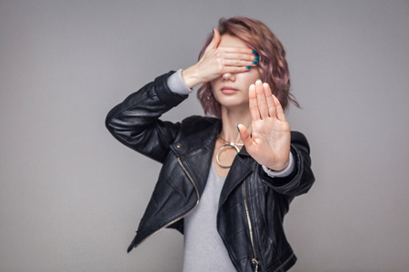 Stop, I dont want to see. Portrait of blocking girl with short hairstyle and makeup in casual style black leather jacket standing with stop gesture. indoor studio shot, isolated on grey background. Banco de Imagens