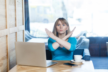 Enough! Portrait of warning aggressive young girl with blonde hair in t-shirt blouse are sitting in cafe and working on laptop and showing crossing raised arms like stop gesture. Indoor