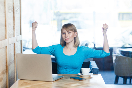 Portrait of beautiful happy satisfied positive young girl freelancer with blonde hair in blue t-shirt are sitting in cafe and made all tasks for work, she triumphing with raised arms,looking at camera Stock Photo