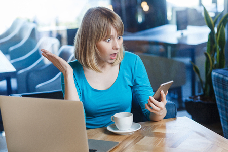 Top view portrait of young shocked blonde woman in blue t-shirt, sitting in cafe and holding her mobile smart phone and looking with amazed face and big eyes with raised hand. indoor studio shot.