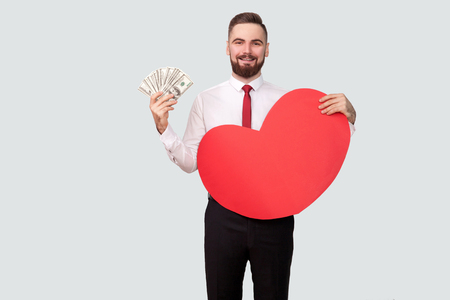 Young bearded man holding many dollars and red heart shape and looking at camera with toothy smile. Indoor, studio shot, isolated on gray background