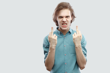 Portrait of angry handsome long haired blonde young man in blue casual shirt standing and looking at camera with middle finger fuck sign. indoor studio shot, isolated on light grey background.