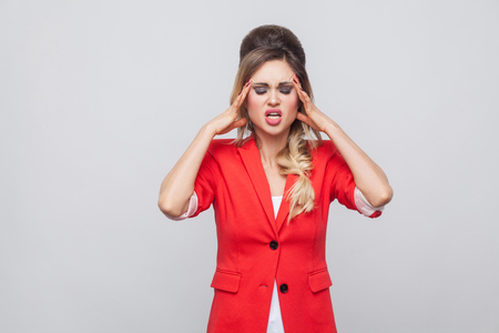 Portrait of sick beautiful business lady with hairstyle and makeup in red fancy blazer standing, holding her head and feeling headache. indoor studio shot, isolated on grey background.