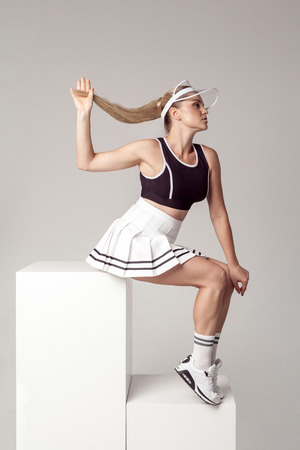 Side view portrait of attractive athletic young woman in fashionable tennis sportwear siting on white cube and posing beautiful perfect figure. Studio shot, indoor, grey background. Sporty concept.