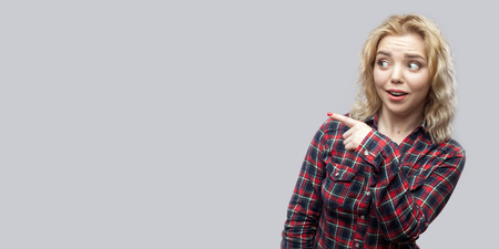 Portrait of surprised young beautiful blonde woman in casual red checkered shirt standing looking and pointing at copyspace. indoor studio shot, isolated on grey background. Reklamní fotografie