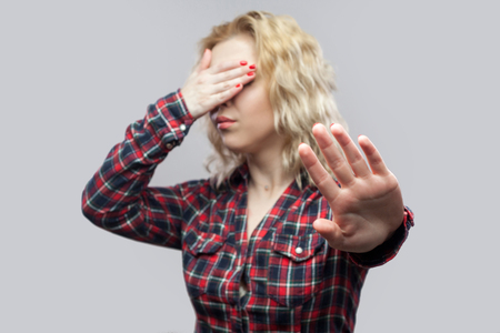 Stop, i dont want to see this. Portrait of beautiful blonde young woman in casual red checkered shirt standing with stop gesture and covering her eyes. studio shot, isolated on grey background. Banco de Imagens
