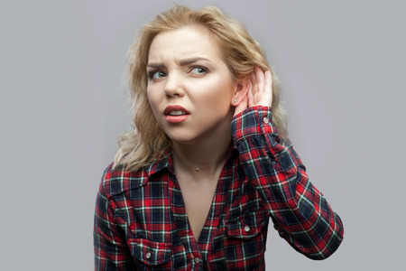 Portrait of nosy beautiful blonde young woman in casual red checkered shirt standing with hand near ear and trying to hear and spying. indoor studio shot, isolated on grey background.