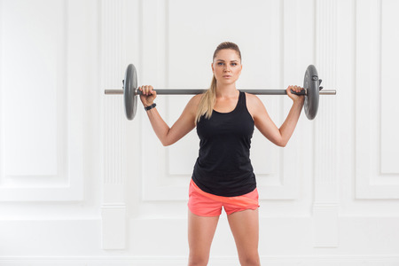 Portrait of young athletic beautiful bodybuilder woman in pink shorts and black top doing squats and exercising at the gym with the barbell on white wall. indoor, studio shot, looking at camera