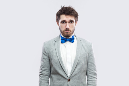 Portrait of alone handsome bearded man in casual grey suit and blue bow tie standing and looking at camera with sad eyes. indoor studio shot, isolated on light grey background.