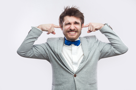 I don't want to hear. Portrait of worried handsome bearded man in casual grey suit, blue bow tie standing with closed eyes and putting fingers in ears. studio shot, isolated on light grey background. Stock Photo