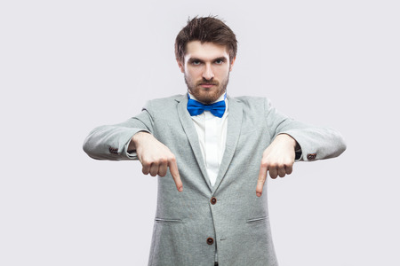 Here and right now. Portrait of serious bossy handsome bearded man in casual grey suit and blue bow tie standing pointing and looking at camera. indoor studio shot, isolated on light grey background.