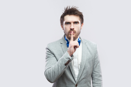 Portrait of serious handsome bearded man in casual grey suit and blue bow tie standing, looking at camera with silence sign. indoor studio shot, isolated on light grey background. Stock Photo