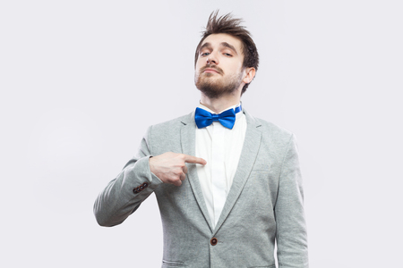 Portrait of proud satisfied haughty handsome bearded man in casual grey suit and blue bow tie standing, pointing himself and looking at camera. indoor studio shot, isolated on light grey background. Stock Photo