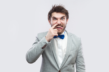 Portrait of funny handsome bearded man in casual grey suit and blue bow tie standing and looking at camera with tongue out and drilling nose. indoor studio shot, isolated on light grey background.