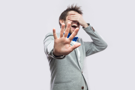 Stop, i don't want to see this. Portrait of shocked or scared young bearded man in casual grey suit standing closed eyes and blocking with hand. indoor studio shot, isolated on light grey background.