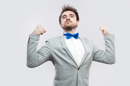I am strong and independent. Portrait of satisfied proud handsome bearded man in casual grey suit and blue bow tie standing and looking at camera. indoor studio shot, isolated on light grey background